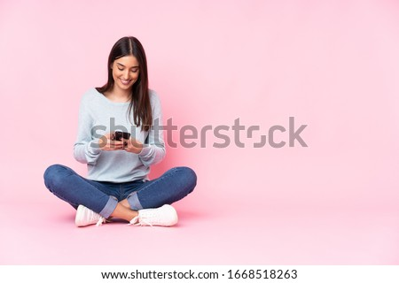 Young caucasian woman isolated on pink background sending a message with the mobile