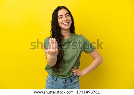 Young caucasian woman isolated on yellow background inviting to come with hand. Happy that you came Сток-фото ©