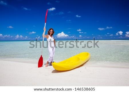 Young caucasian woman keeps paddle at the seashore near yellow kayak