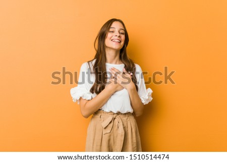 Young caucasian woman laughing keeping hands on heart, concept of happiness.