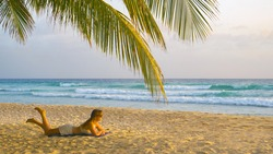 Young Caucasian woman lies on the tropical white sand beach and watches the surfers catching waves. Tourist girl relaxes on the scenic coastline of Barbados and observes the approaching ocean waves.