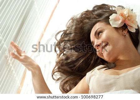 Young Caucasian woman lying in bed with flowers on a light background