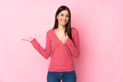 Young caucasian woman over isolated background holding copyspace imaginary on the palm to insert an ad and with thumbs up