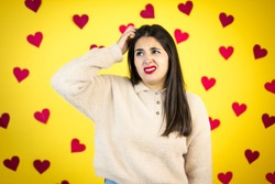 Young caucasian woman over yellow background with red hearts confuse and wonder about question. Uncertain with doubt, thinking with hand on head