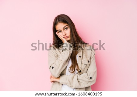 Young caucasian woman posing in a pink background who is bored, fatigued and need a relax day.