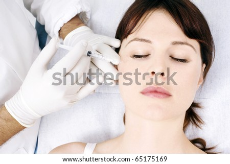 young caucasian woman receiving an injection from a doctor