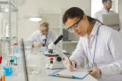 Young caucasian woman scientist in protective goggles making notes in report on clipboard sitting at desk with microscope. Female researcher working on vaccine development at biochemistry laboratory