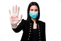Young Caucasian woman showing  gloves standing over isolated white background with open hand doing stop sign. Corona virus concept. Don't touch.