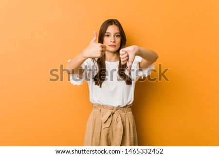 Young caucasian woman showing thumbs up and thumbs down, difficult choose concept