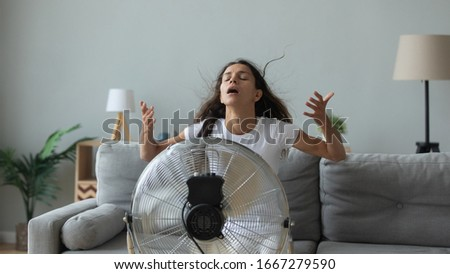 Young Caucasian woman sit on couch in living room breathe fresh air from floor fan suffering from lack of conditioner, millennial girl use ventilator struggle with home heat, summer hot weather