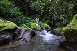 Young Caucasian woman sitting on the rock near the river in Vajrasana o Diamond pose. Hands raising up in namaste mudra. Tropical nature landscape. Yoga and pranayama concept. Calm relaxing mood.
