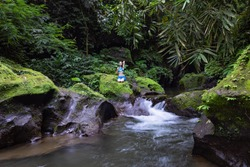 Young Caucasian woman sitting on the rock near the river in Vajrasana or Diamond pose. Hands hooked behind the back. Tropical nature landscape. Yoga retreat. Calm relaxing mood. Bali.