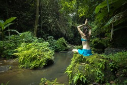 Young Caucasian woman sitting on the rock, practicing yoga and pranayama. Raising arms with namaste mudra. View from back. Vacation in Asia. Calm and relaxing atmosphere. Yoga retreat. Bangli, Bali.