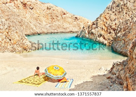 young caucasian woman sitting with her back to the camera on wild beach of Seitan Limania, Chania on sunny summer day, Crete, Greece