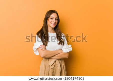 Young caucasian woman smiling confident with crossed arms.