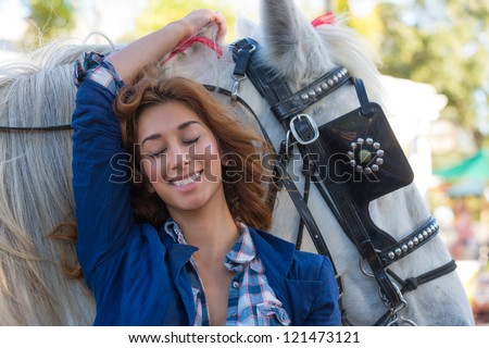 Young caucasian woman smiling very happy with horse.