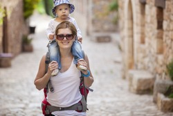 Young Caucasian woman tourist carrying her little son on shoulders