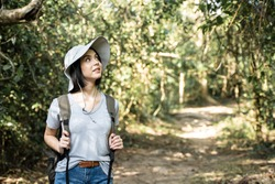Young Caucasian woman traveling in the forest alone. The girl is feeling fresh, wonderful exciting and relax in nature wild, looking around the view then continue walking with happiness and fun.