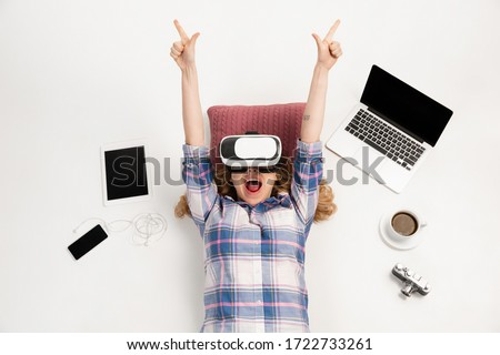Young caucasian woman using devices, gadgets isolated on white studio background. Concept of modern technologies, gadgets, tech, emotions, ad. Copyspace. Gaming, shopping, meeting online education. Stock photo ©