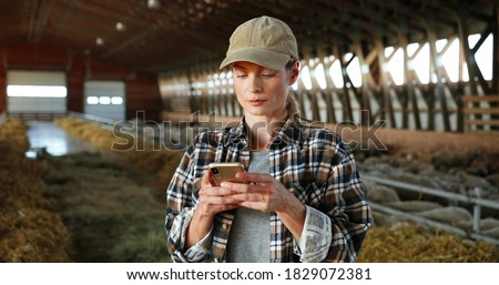Young Caucasian woman using smartphone and working in farm stable. Female farmer tapping and scrolling on mobile phone in shed. Shepherd texting message on telephone. Farming concept.
