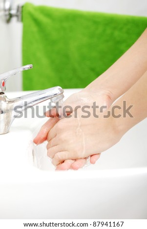 Young caucasian woman washing hands in bathroom.