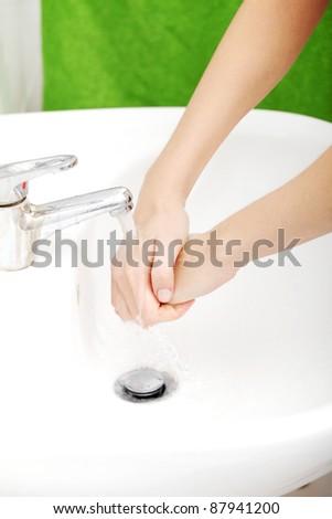 Young caucasian woman washing hands in bathroom.