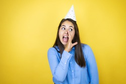 Young caucasian woman wearing a birthday hat over isolated yellow background hand on mouth telling secret rumor, whispering malicious talk conversation