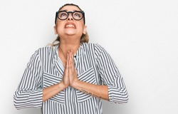 Young caucasian woman wearing business shirt and glasses begging and praying with hands together with hope expression on face very emotional and worried. begging.