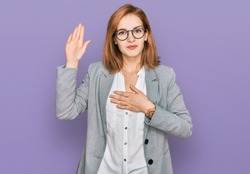 Young caucasian woman wearing business style and glasses swearing with hand on chest and open palm, making a loyalty promise oath