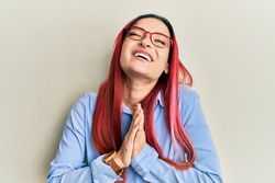 Young caucasian woman wearing casual clothes and glasses begging and praying with hands together with hope expression on face very emotional and worried. begging.
