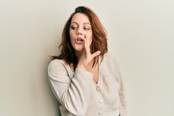 Young caucasian woman wearing casual clothes hand on mouth telling secret rumor, whispering malicious talk conversation