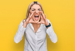 Young caucasian woman wearing casual clothes shouting angry out loud with hands over mouth