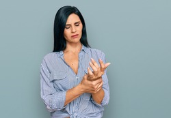 Young caucasian woman wearing casual clothes suffering pain on hands and fingers, arthritis inflammation