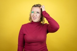 Young caucasian woman wearing casual red t-shirt over yellow background confuse and wonder about question. Uncertain with doubt, thinking with hand on head