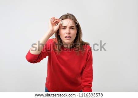 Young caucasian woman wearing glasses looking at camera with doubt and distrust. Problem with eyes, health care concept #1116393578