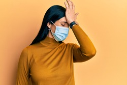 Young caucasian woman wearing medical mask surprised with hand on head for mistake, remember error. forgot, bad memory concept.