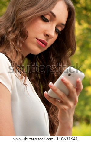 Young caucasian woman with a cell phone in park