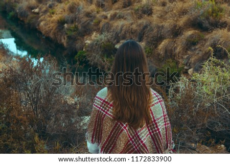 Young caucasian woman with long chestnut hair in checkered wool plaid looks at river standing in field meadow. Cozy autumn atmosphere. Beautiful landscape. Warm earthy colors hipster style
