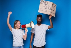 Young caucasian woman with megaphone and African man holding a cardboard poster with the message text END RACISM on blue background.