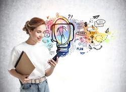 Young caucasian woman with phone and notes, smiling standing on background of colourful light bulb on a concrete wall. Concept of fresh new idea, plan