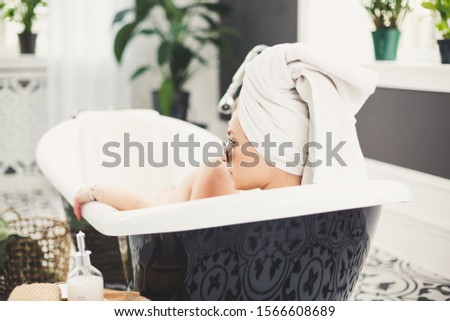 Young caucasian woman with towel on head and sunglasses getting spa treatment in a beauty salon, inside an interior room. Relaxing in the bathroom in linen. The concept of body care and relaxation.
