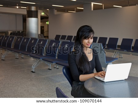 Young Caucasian woman working with her notebook in the airport terminal.