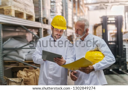 Young Caucasian worker with helmet on head showing statistics on tablet to his older coworker. Coworker holding folder and helmet. #1302849274