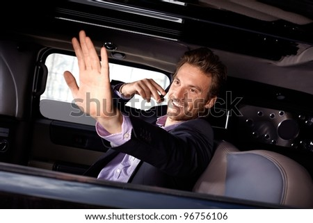 Young celebrity waving from limousine, talking on mobile phone, smiling.?