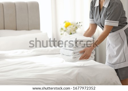 Young chambermaid putting stack of fresh towels in bedroom, closeup. Space for text Сток-фото ©