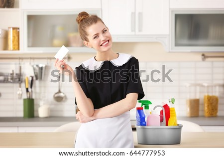 Young chambermaid with business card in kitchen Сток-фото ©
