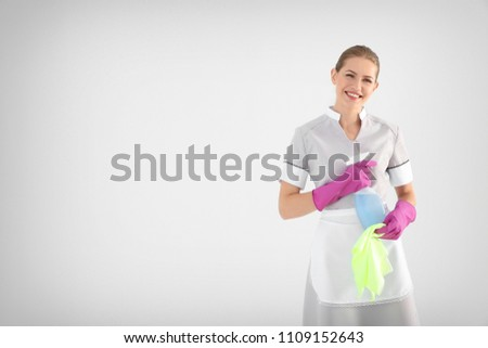 Young chambermaid with rag and detergent on white background