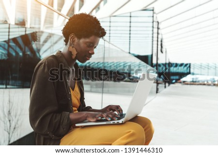 Young charming African female entrepreneur with laptop is sitting on the bench outdoors of her business office area; black female is using her netbook on the street, with copy space area on the right