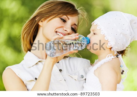 young charming caring mother gives daughter drink water bottles background summer green park