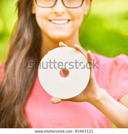 Young charming dark-haired woman holds multimedia disk and smiles, in green summer city park.